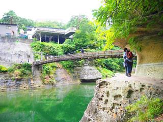 川に橋を渡って歩く男の写真・画像素材[1506713]
