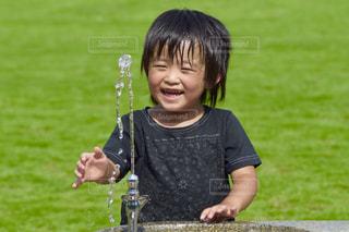 芝生に座っている小さな男の子の写真・画像素材[1009056]