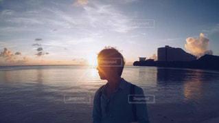水の体の横に立っている人の写真・画像素材[1001500]