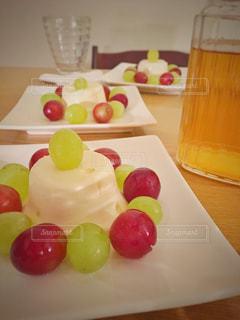 テーブルの上のレアチーズケーキとぶどう盛り合わせの写真・画像素材[990341]