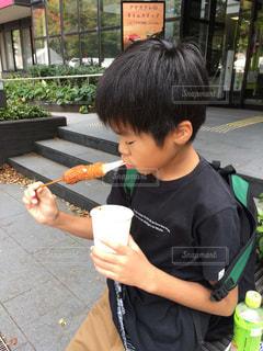 チーズハットグを食べる少年の写真・画像素材[2721357]