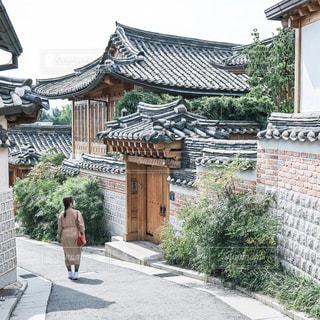 建物の前の歩道を歩いている人の写真・画像素材[3031384]