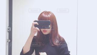 カメラにポーズ鏡の前に立っている女性 - No.990527