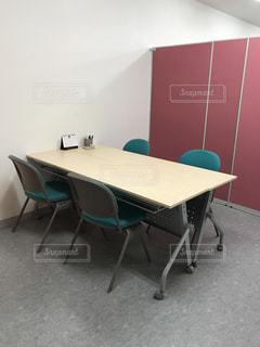 テーブルの前で座っている椅子の写真・画像素材[1091843]
