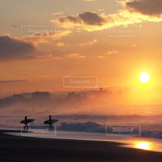 ビーチでの背景の夕日に人々 のグループの写真・画像素材[991205]