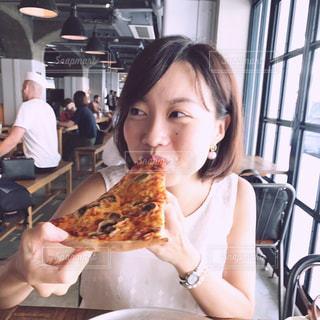 大きなピザを食べる女の写真・画像素材[722289]