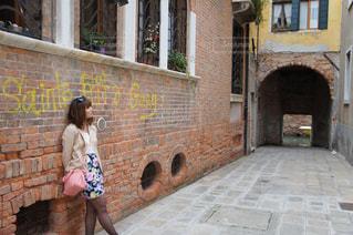 レンガの壁にもたれる女性の写真・画像素材[994220]