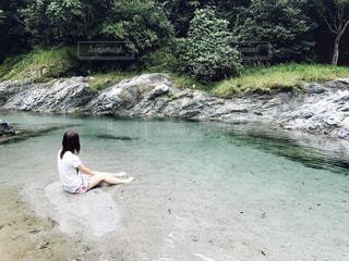 綺麗な川に座る女性の写真・画像素材[1054805]