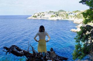 木の上から海を眺める女性の写真・画像素材[1054836]