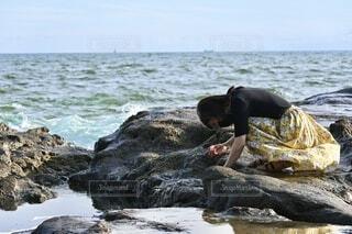 海の近くの岩で磯遊びをする女性の写真・画像素材[4669202]