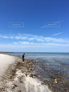 水の体の近くのビーチに立っている人 - No.1185026
