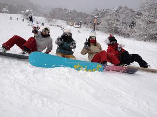 雪の中で座っている人々 のグループの写真・画像素材[995223]