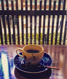 木製のテーブルの上にコーヒーカップの写真・画像素材[1001606]