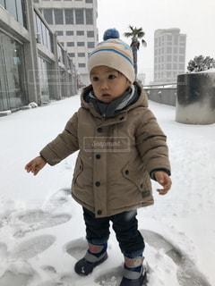 雪の中で立っている少年の写真・画像素材[999453]