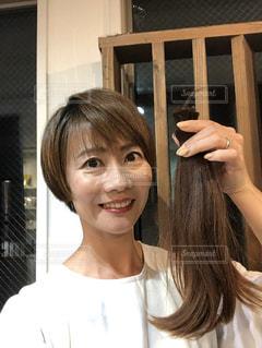 ヘアドネーションの髪の毛たばを持って記念撮影の写真・画像素材[2733735]