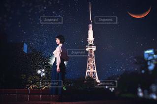暗闇の中で東京タワーを背景に立っている女性の写真・画像素材[999546]