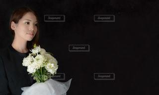 葬儀で花束を持つ女性の写真・画像素材[999550]