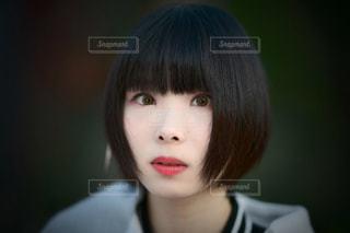 白いシャツと、カメラ目線の女性の写真・画像素材[1001962]
