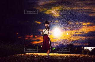 夕日をバックにバイオリンを弾く女性の写真・画像素材[1001965]