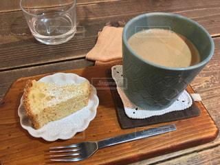 木製テーブルの上のコーヒー カップの横にパンの切れ端の写真・画像素材[1006829]