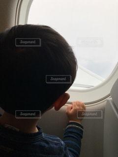 飛行機の窓から外を見る少年の写真・画像素材[1165975]