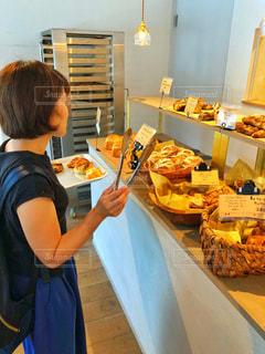 ベーカリーでパンを選ぶ女性の写真・画像素材[1415574]