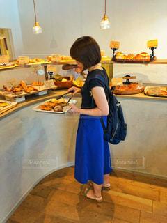 お気に入りのベーカリーでパンを選ぶ女性の写真・画像素材[1415575]