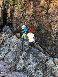 岩の上に乗って遊ぶ兄弟の写真・画像素材[1428913]