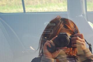 窓の前でカメラを持っている人の写真・画像素材[1705953]