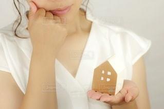家の模型を手に取る女性の写真・画像素材[3560112]
