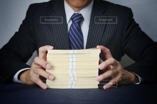 スーツ姿の男性と現金の写真・画像素材[3611698]