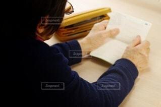通帳を見つめる高齢女性の写真・画像素材[3941572]