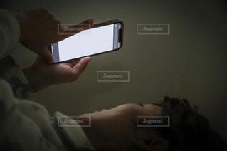 暗がりでスマホ操作する女性の写真・画像素材[4284319]