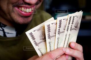 お金を見て笑う男性の写真・画像素材[4308699]