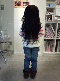 本の棚の前に立っている女の子の写真・画像素材[1007619]