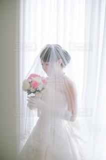 ウィンドウの前面に立っているピンクのドレスの女性の写真・画像素材[1135413]