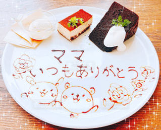 テーブルの上にケーキをトッピングした白い皿の写真・画像素材[2259446]