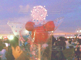 夏祭りの花火とミッキーのりんご飴の写真・画像素材[1008852]