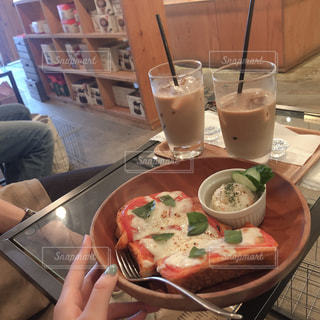 食べ物のあるテーブルに座っている人の写真・画像素材[2330154]