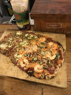 木製のまな板にピザのスライスの写真・画像素材[1008855]