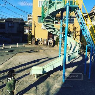 大きい滑り台を眺める少年の写真・画像素材[1009825]