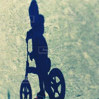 ストライダーに乗る少年の影の写真・画像素材[1009826]