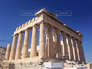 パルテノン神殿の側に時計と大きな背の高い塔の写真・画像素材[1010061]
