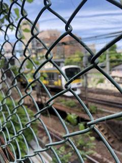 ワイヤーフェンスの向こうの電車の写真・画像素材[4396465]
