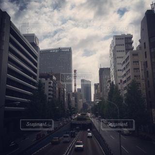 背の高い建物に囲まれたトラフィックでいっぱい街の通りのビューの写真・画像素材[1014687]