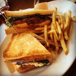 近くにサンドイッチと皿にフライド ポテトのの写真・画像素材[1017024]