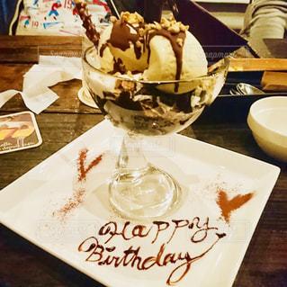 皿の上のケーキをテーブルに着席した人 - No.1052313