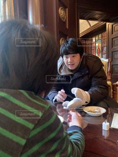 食べ物を食べているテーブルに座っている人の写真・画像素材[2870256]