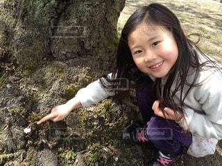 木の隣に立っている女の子の写真・画像素材[1022119]