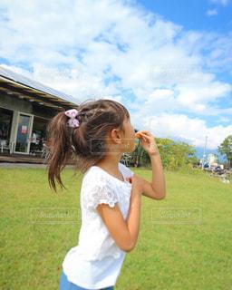 フィールドに電話で話している若い女の子の写真・画像素材[1035182]